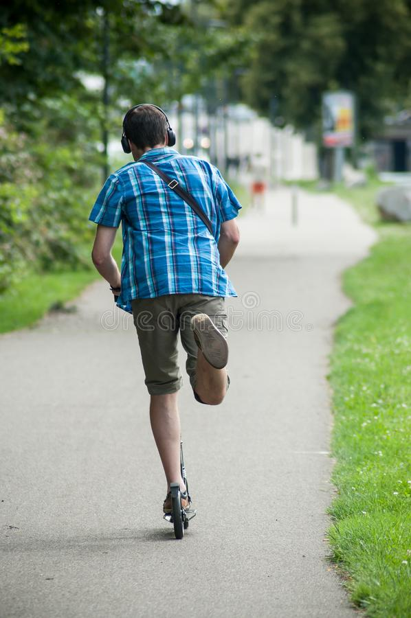 Портрет человека на самокате на дороге с наушниками на заднем v стоковое фото rf