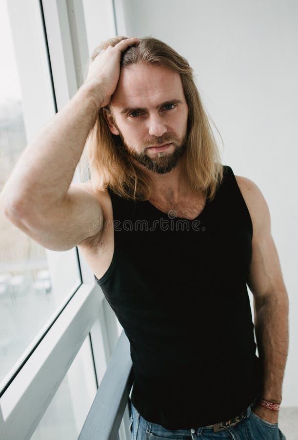 Портрет человека при длинные светлые волосы смотря в камере Портрет крупного плана молодого мальчика представляя в белой предпосы стоковые изображения rf