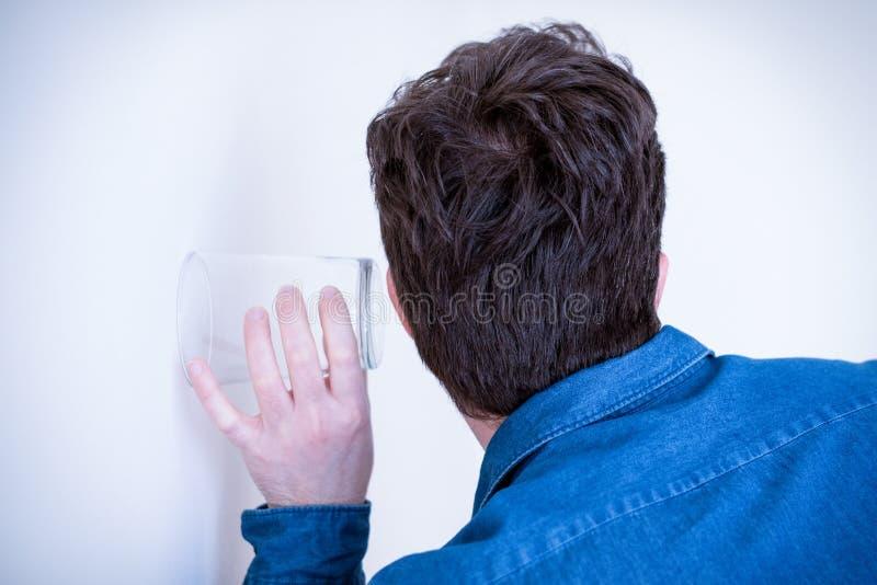 Портрет человека слушая и шпионя через стену стоковая фотография