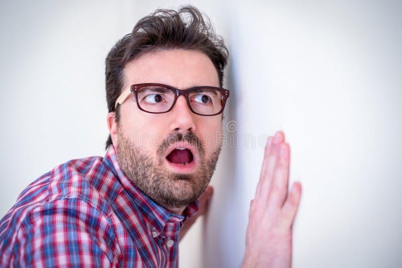 Портрет человека слушая и шпионя через стену стоковые изображения