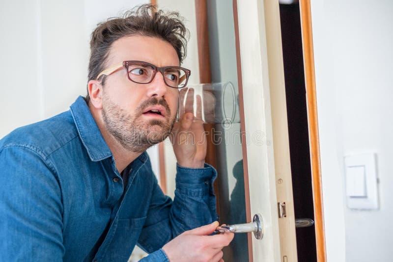 Портрет человека слушая и шпионя через стену стоковое изображение rf