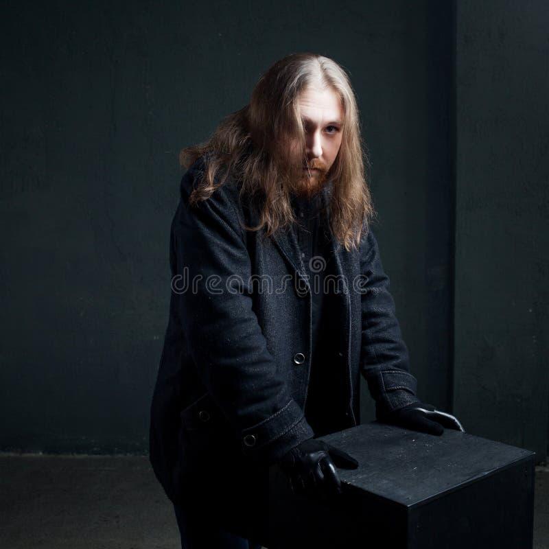 Портрет человека с длинными волосами и бороды в черных одеждах на темной предпосылке стоковая фотография