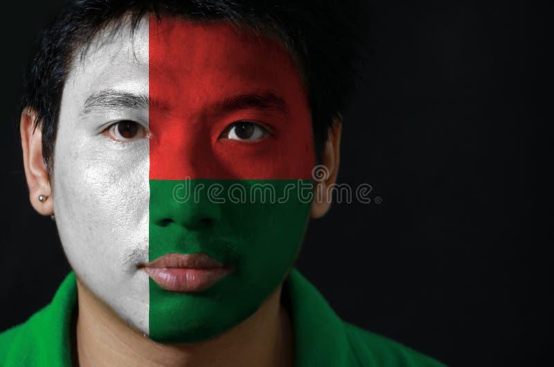 Портрет человека с флагом Мадагаскара покрасил на его стороне на черной предпосылке стоковые изображения