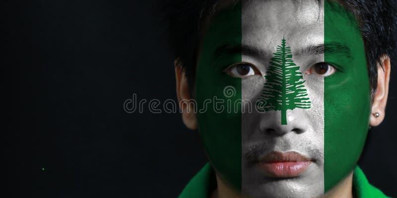 Портрет человека с флагом Острова Норфолк покрасил на его стороне на черной предпосылке стоковые изображения rf