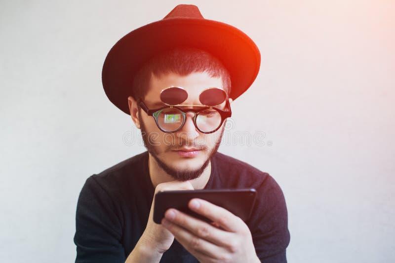 Портрет человека хипстера бородатого используя smarphone над белой предпосылкой стоковая фотография