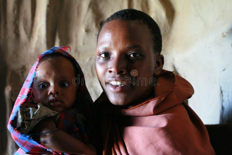 Портрет чернокожей женщины с младенцем внутри племени Maasai хат стоковые фотографии rf
