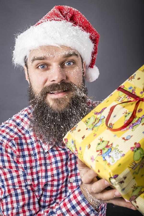 Портрет человека при шляпа santa держа подарок стоковое изображение