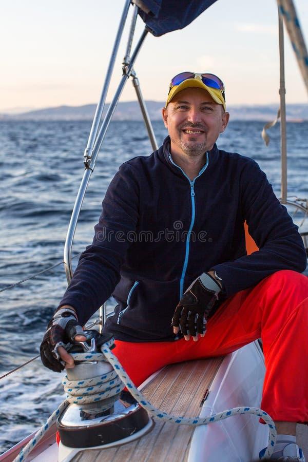 Портрет человека сидит на его яхте ветрила Спорт стоковое изображение rf