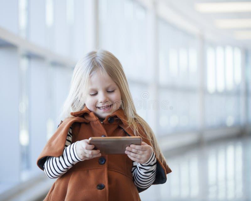 Портрет шаржа жизнерадостной маленькой девочки наблюдая на smartphone стоковые изображения rf