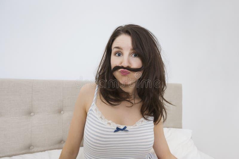 Портрет шаловливой женщины при усик сделанный из волос в кровати стоковые изображения
