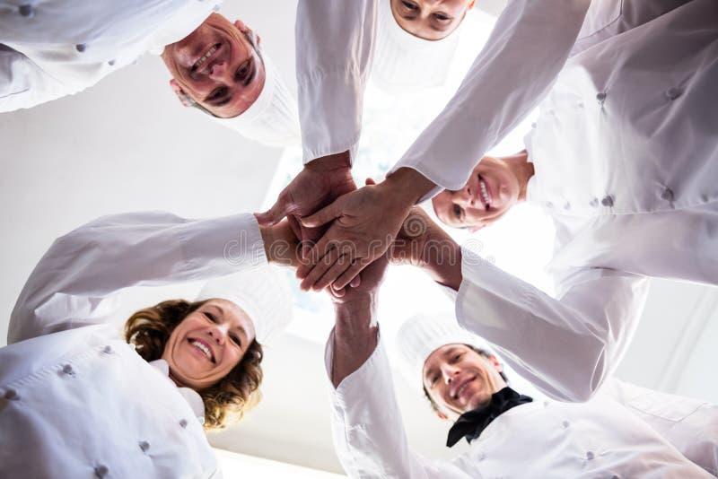 Портрет шеф-поваров объединяется в команду кладущ руки совместно и веселить стоковое фото rf
