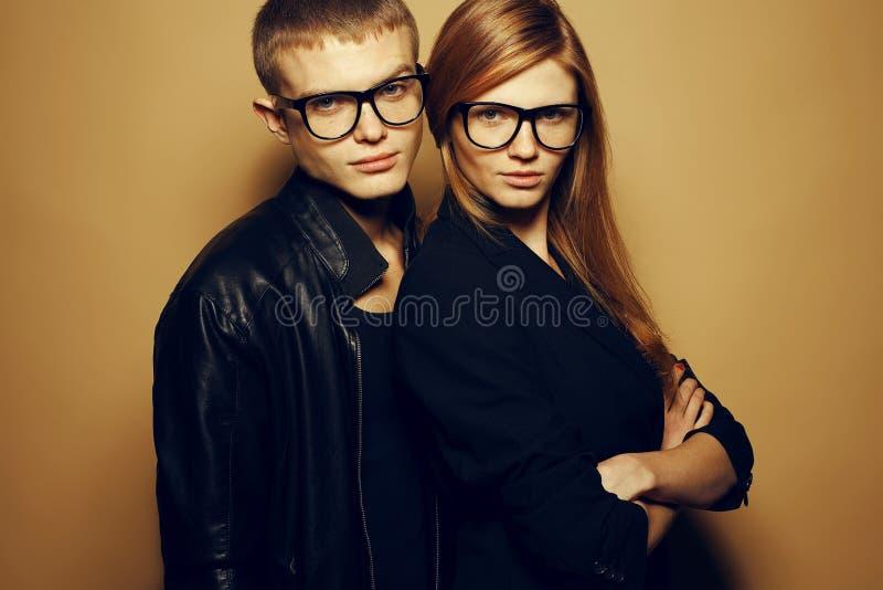 Портрет шикарных рыжеволосых близнецов моды в черных одеждах нося ультрамодные стекла и представляя над бежевой предпосылкой совм стоковое изображение