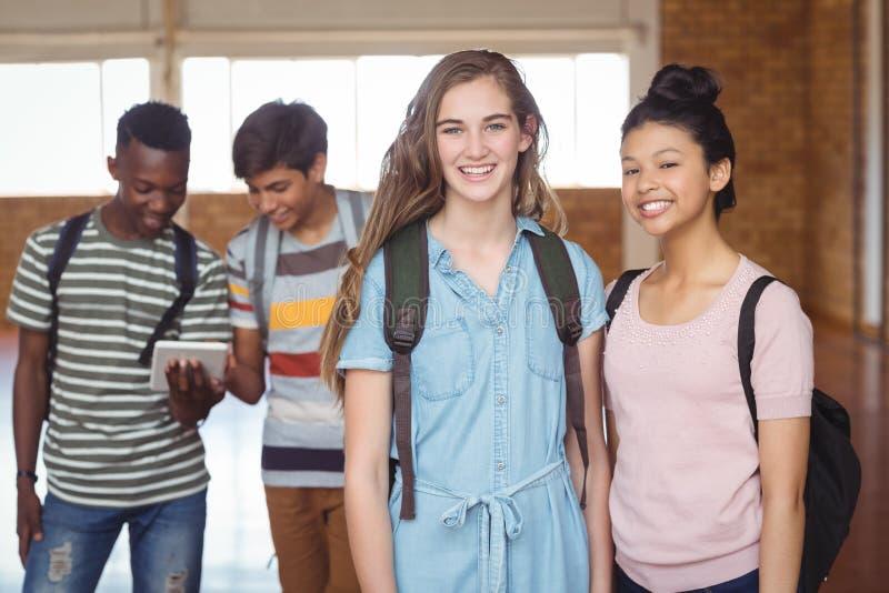 Портрет школьниц стоя с одноклассником с одноклассниками в предпосылке стоковое изображение