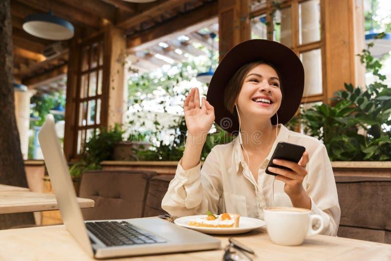 Портрет шляпы молодой женщины нося используя смартфон и наушники стоковое фото rf
