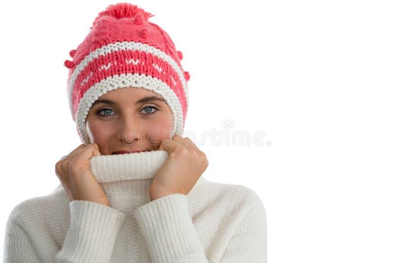 Портрет шляпы knit женщины нося пока покрывающ сторону с свитером turtleneck стоковая фотография rf