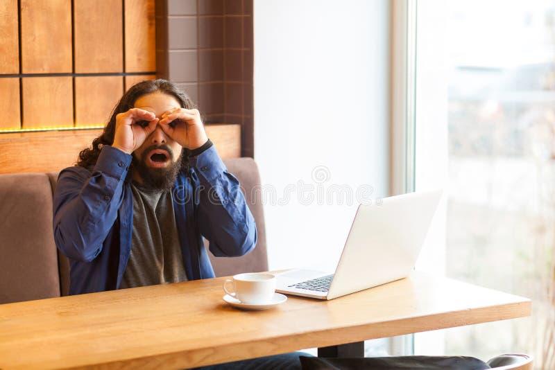 Портрет шпионить красивый молодой взрослый фрилансер человека в непринужденном стиле сидя в кафе с ноутбуком, держащ руку около г стоковые изображения rf