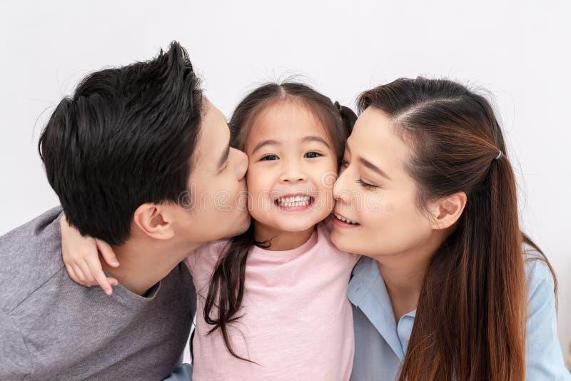 Портрет щеки привлекательной азиатской семьи целуя совместно близкой вверх на изолированной белой предпосылке студии Альфа и mill стоковая фотография rf