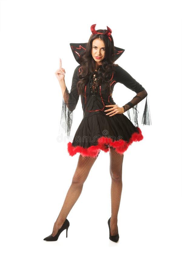 Портрет дьявола женщины нося одевает указывать вверх стоковое изображение