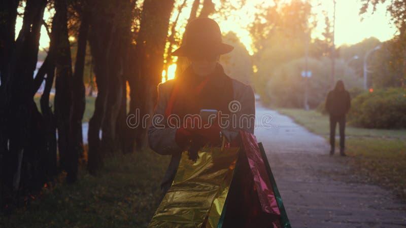 Портрет элегантной зрелой старухи используя умный телефон идет от торгового центра с сумками в парке осени во время захода солнца стоковое изображение
