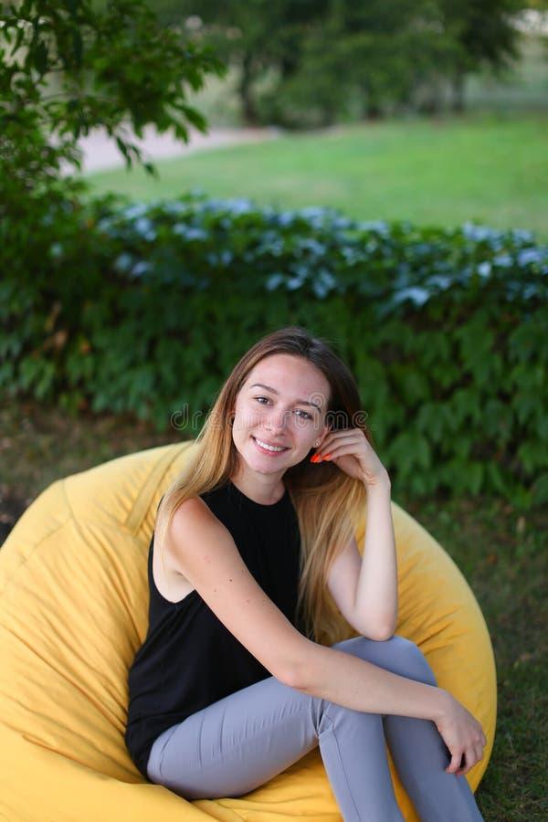 Портрет alluring девушки усмехаясь на камере и фотограф сидят стоковая фотография rf