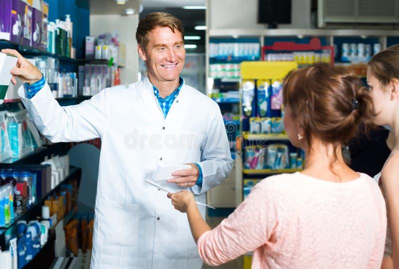 Портрет druggist человека в белом пальто давая совет к клиенту стоковая фотография
