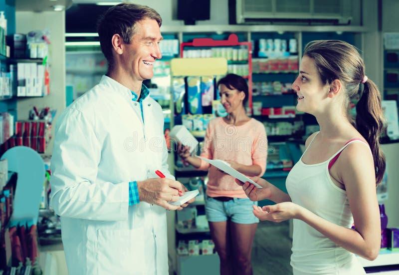 Портрет druggist человека в белом пальто давая совет к клиенту стоковое изображение