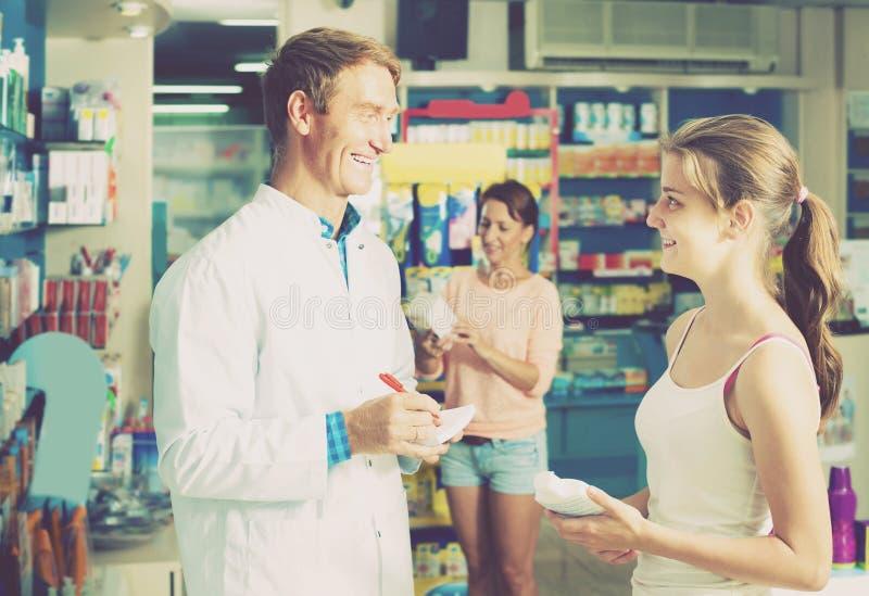 Портрет druggist человека в белом пальто давая совет к клиенту стоковое фото rf