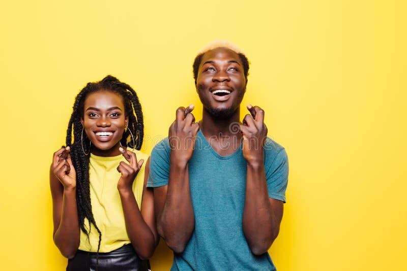 Портрет excited молодой африканской пары стоя совместно и перекрестных пальцев вверх на космосе экземпляра изолированном над бело стоковые фото