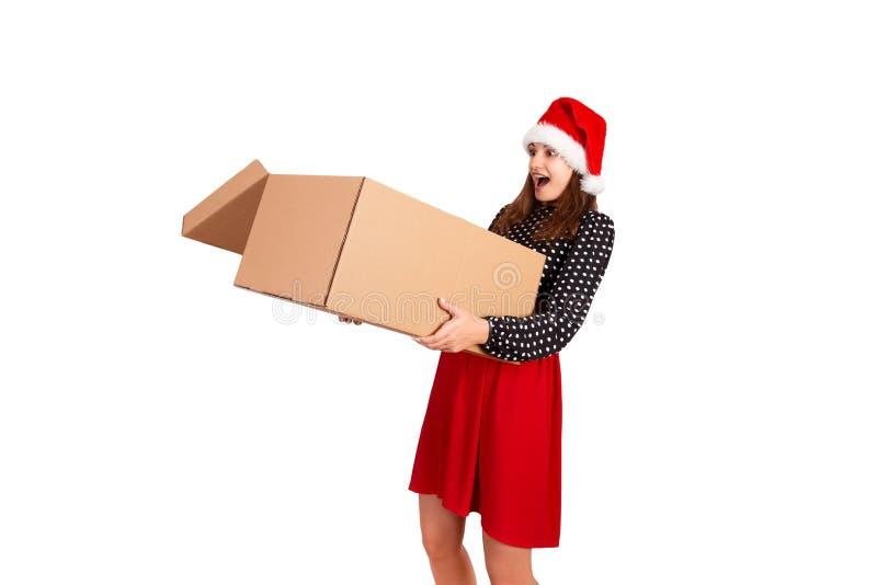 Портрет excited удивленной девушки в платье держа большую и тяжелую открытую подарочную коробку белизна изолированная предпосылко стоковые фото