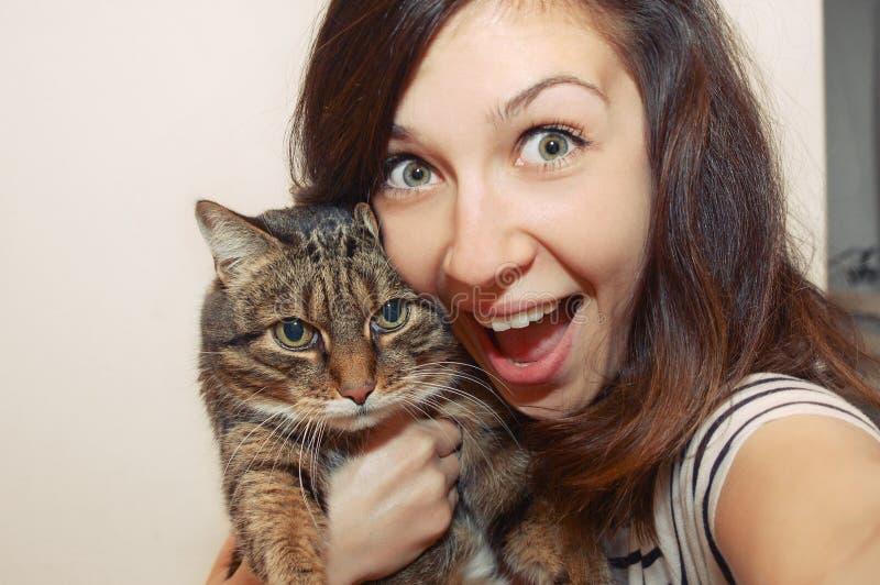 Портрет fuuny усмехаясь девушки с котом стоковое фото