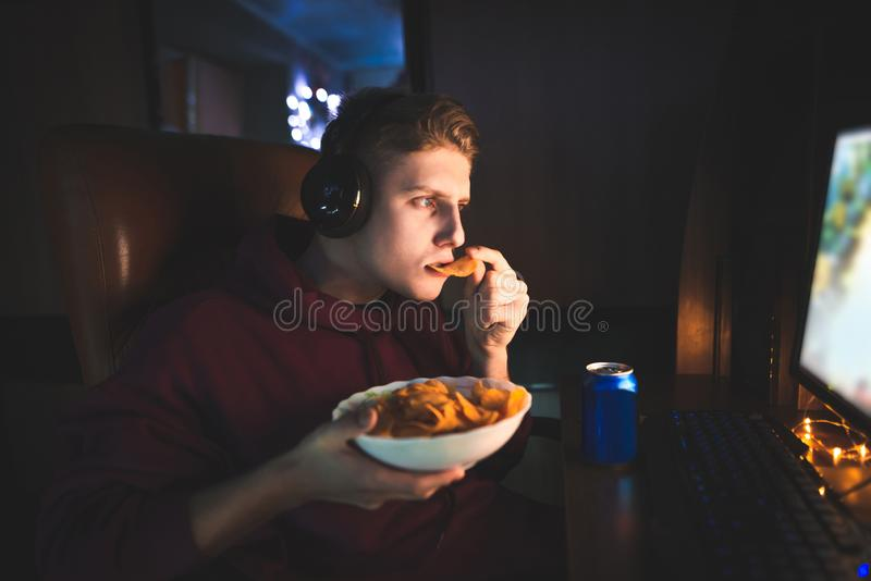 Портрет gamer играя видеоигры на компьютере и есть закуски стоковые изображения