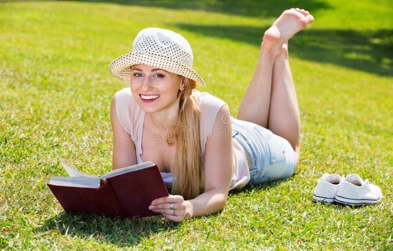 Портрет l женщины лежа на зеленой лужайке в книге парка и чтения стоковое фото