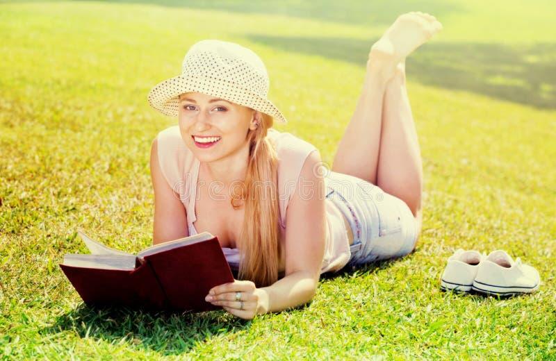 Портрет l женщины лежа на зеленой лужайке в книге парка и чтения стоковая фотография