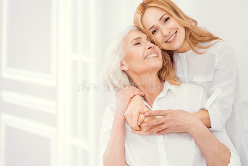 Портрет loveful зрелой дочери обнимая ее пожилую маму стоковое фото