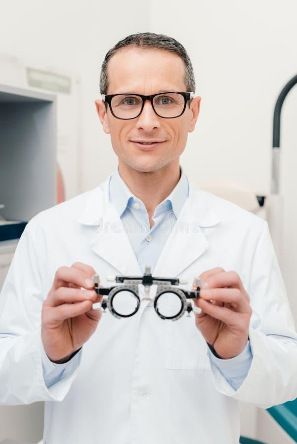 портрет optometrist в белом пальто держа пробную рамку в руках стоковые изображения rf
