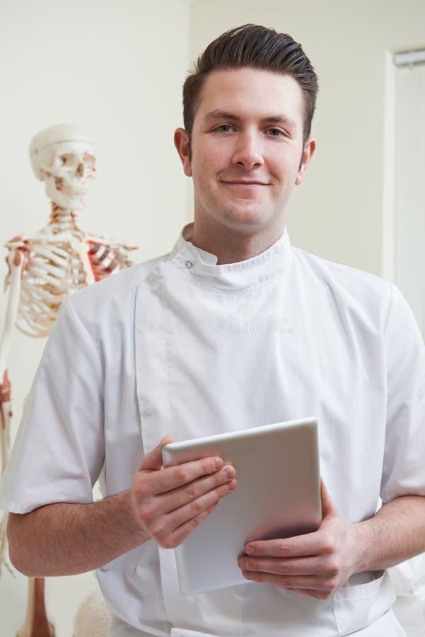 Портрет Osteopath в кабинете врача с таблеткой цифров стоковое фото rf