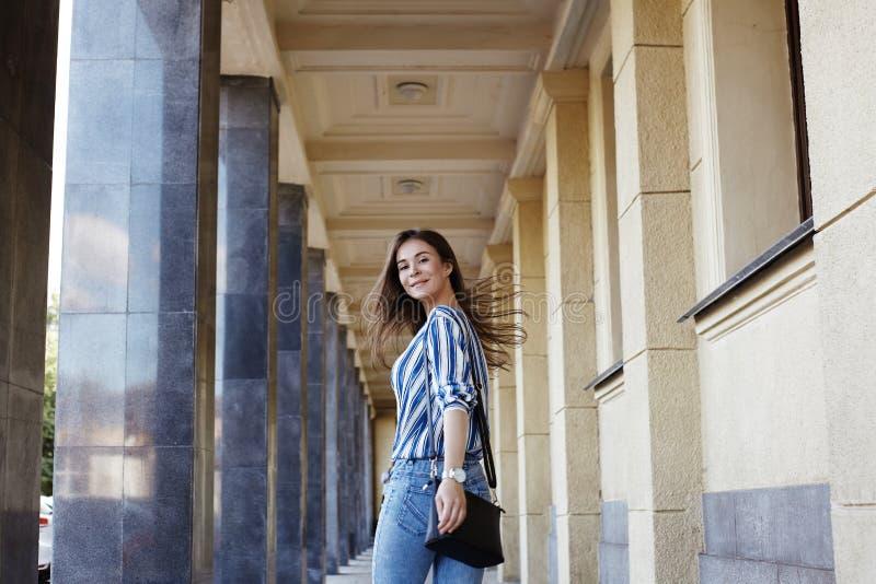 Портрет Outdoors стиля улицы милой девушки женщина способа сь Она нося рубашка печати, джинсы, сумка счастливый уклад жизни стоковое изображение rf