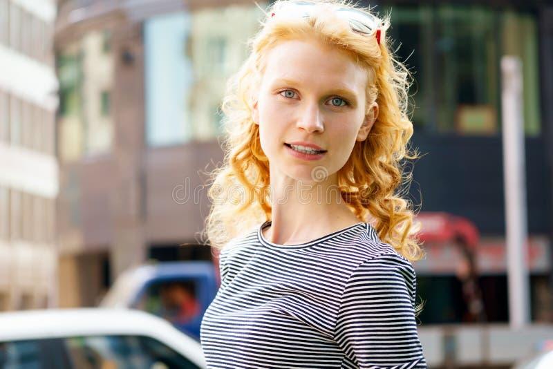 Портрет redheaded усмехаясь девушки на городской предпосылке стоковое изображение