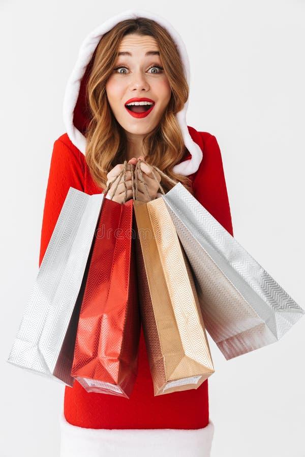 Портрет shopaholic женщины 20s нося костюм Санта Клауса красный усмехаясь и держа красочные бумажные хозяйственные сумки с приобр стоковые фотографии rf