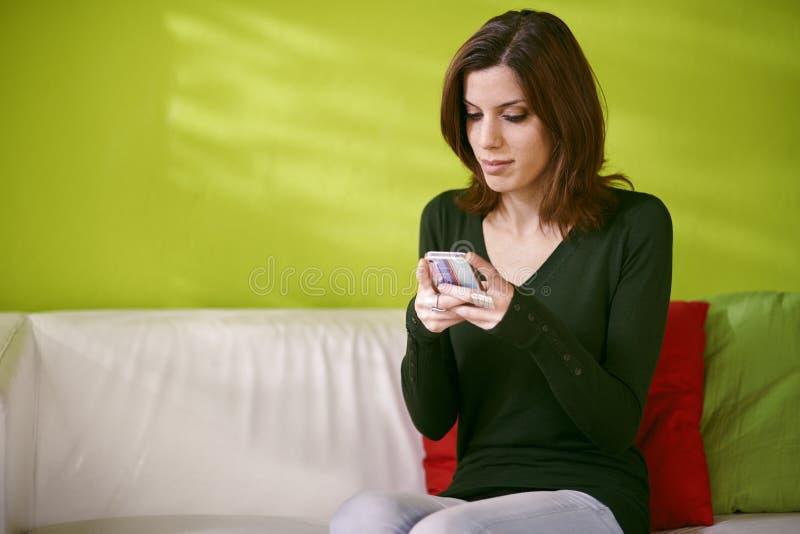 Портрет sms чтения девушки на smarthphone дома стоковые изображения