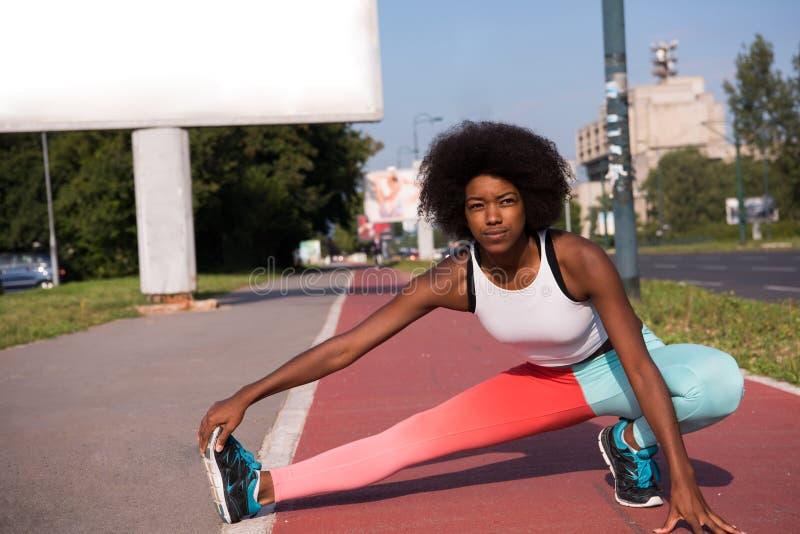 Портрет sporty молодой Афро-американский протягивать женщины переплюнет стоковое изображение
