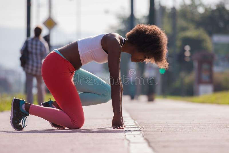 Портрет sporty молодой Афро-американский протягивать женщины переплюнет стоковые изображения