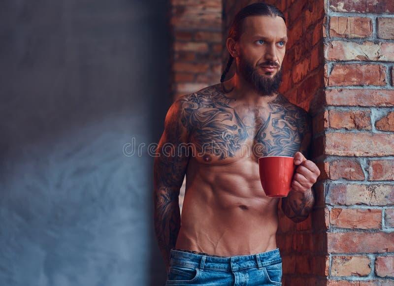 Портрет tattoed без рубашки мужчины с стильными стрижкой и бородой, кофе утра пить, полагаясь против кирпича стоковые изображения rf