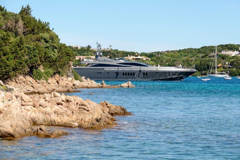 ПОРТУ CERVO, SARDINIA/ITALY - 19-ОЕ МАЯ: Роскошная яхта покидая порт стоковые фотографии rf