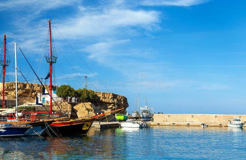 Порт Hersonissos с шлюпками в открытом море и холмах на предпосылке, острове Крита, Греции стоковые фотографии rf