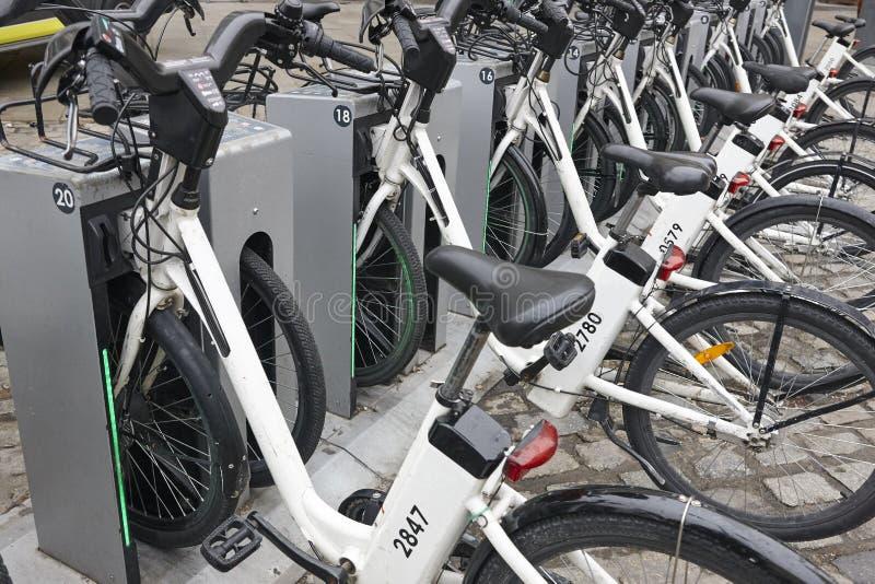 Поручая электрические велосипеды в городе Городской зеленый транспорт стоковое фото