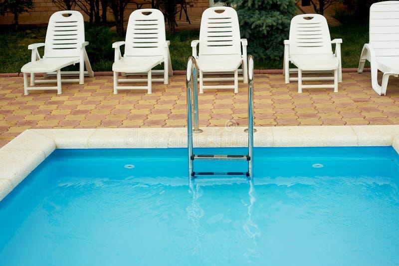 Поручни металла в бассейне с шезлонгами Спуск в воду Каникулы, остатки и релаксация стоковое изображение rf