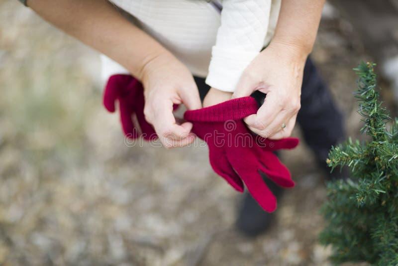 Порция матери положила красные Mittens на ребенка стоковые фото