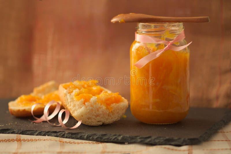 Порция полого хлеба с домашним оранжевым мармеладом и закругленным фоном стоковое изображение rf
