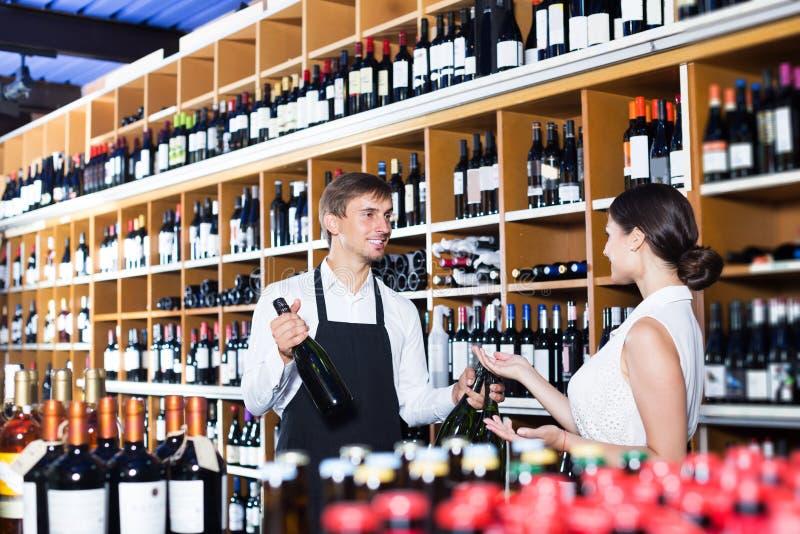 Порция продавца для того чтобы купить бутылку стоковые изображения